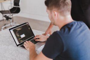 Mann programmiert an Laptop