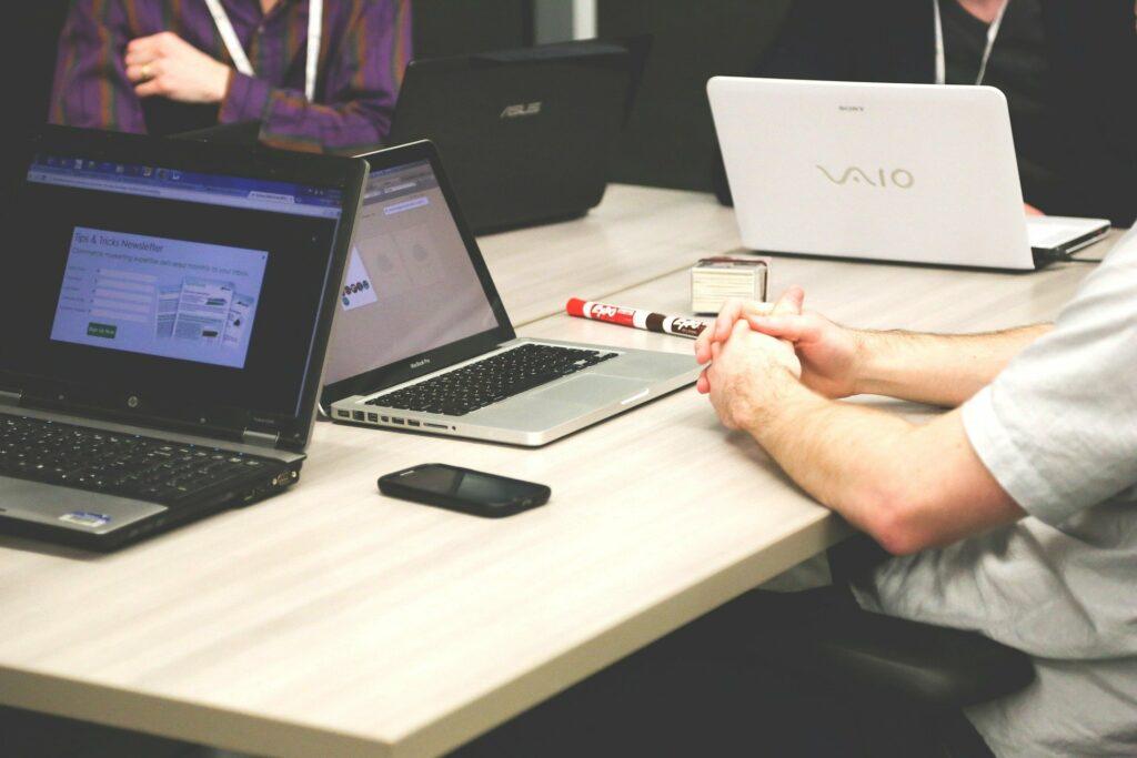 mehrere Laptops auf Tisch während Besprechung